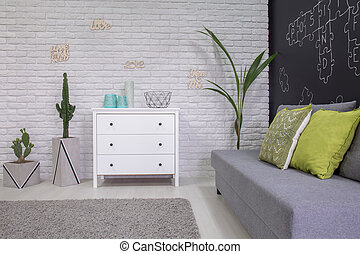 Functional room with decorative houseplants, dresser and...