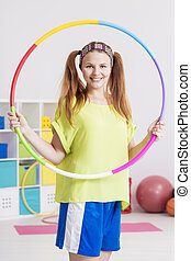 Sportswoman with hula hoop - Young sportswoman holding a...