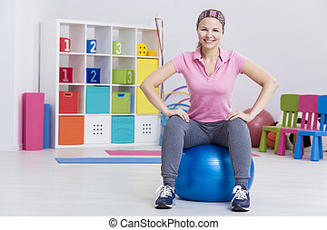 Woman sitting on exercise ball - Fit woman sitting on an...