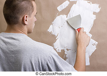 Worker - Caucasian man plastering a brown wall with a pallet...