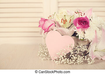 Valentines day flowers in basket and heart shapes card