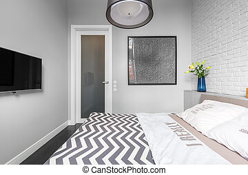 Grey bedroom with tv and double bed