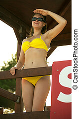 Woman standing on lifeguard tower on the beach.