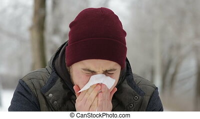 Sick man blowing his nose in winter park - Sick man blowing...