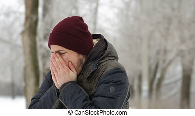 Man coughing winter outdoors in park
