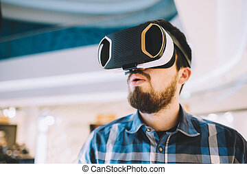 Young man trying vr goggles in the shopping centre - Young...