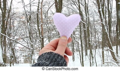 Love Winter idea. Hand holding a heart on the background of the forest.