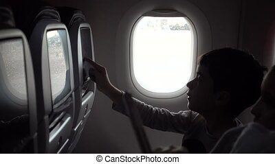 Children on airplane using In flight entertainment known as...