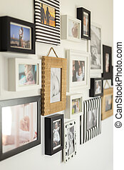 photos of the family in various photo frames - white wall...