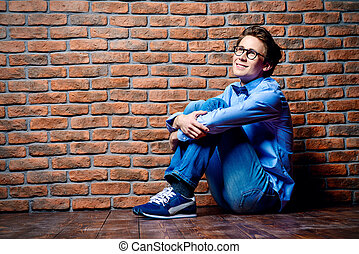 Happy young man sitting on a floor and dreamily looking up....