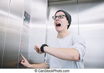 Young stylish guy standing in elevator