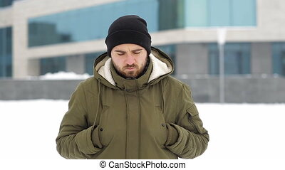 Sad young man in the winter city