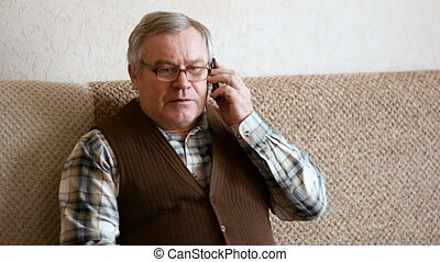 Old man sitting on the couch at home talking on smartphone