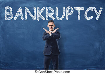 Businessman standing with his hands like cross sign and word 'Bankruptcy' written on blackboard behind him