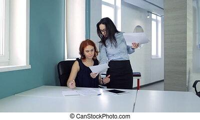 Secretary brings documents to woman boss inside office....