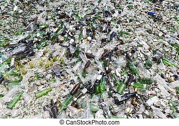 Glass waste in recycling facility. Pile of bottles. - Glass...