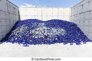 Glass waste in recycling facility. Blue bottles - Glass...