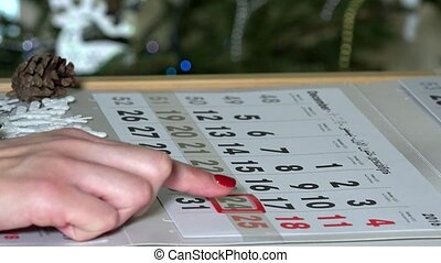 Female woman finger pushing paper calendar marker through...