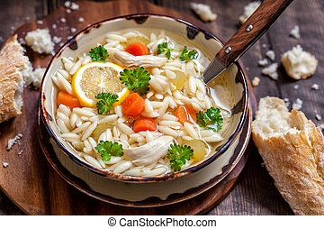 Bowl of Italian Lemon Chicken Orzo Soup. Rustic Style