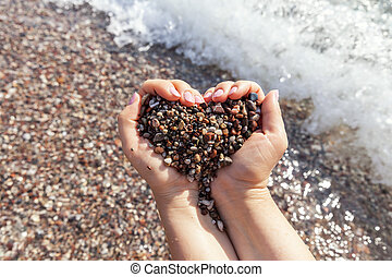 Woman hands holding stones in heart shape