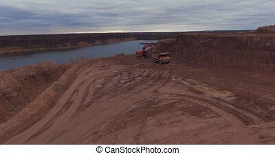 Flight to drone on sand quarry with heavy machinery