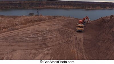 Flight to drone on sand quarry with heavy machinery, the old...