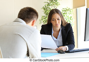 Bad resume in a job interview - Businesswoman reading a bad...