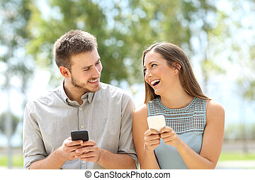 Couple or friends joking with phones - Front view of a...