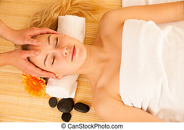 Beautiful blonde woman having a face massage in spa salon