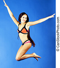 young pretty smiling happy slim jumping girl in bikini on...