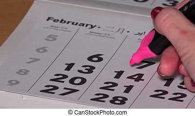 Girl hand with red marker draw a heart shape in the calendar february 14th