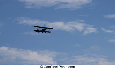 Retro airplane in cloudy sky - Retro plane flying in blue...