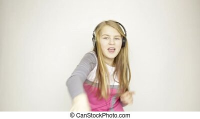 young girl listening music on headphones and funy dancing -...