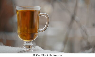 Steaming Cup Of Hot Tea In Snowy Winter