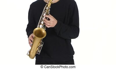 Playing the saxophone in the performance a young male...