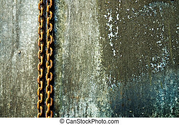 Rusty chain hanging on a weathered wall