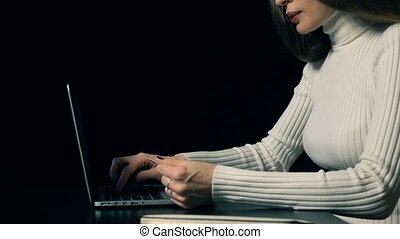 Beautiful brunette woman making payment with her credit card and laptop against black background. Online shopping concept. 4K shot