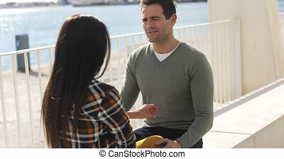 Young man and woman sitting chatting at a quay on a concrete...