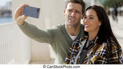 Happy laughing couple taking their selfie on a smartphone as...
