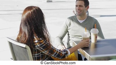 Young couple enjoying takeaway coffee sitting at a...