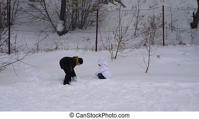 Girl child and teenager boy playing snowballs. Brother and sister having fun in winter park. Frosty winter cloudy day. Slow motion