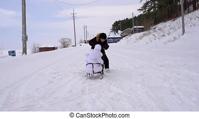 Teen boy sledding girl child. Girl is very happy that her brother sledding. Children are passionate about winter fun. A cloudy winter day. Slow motion