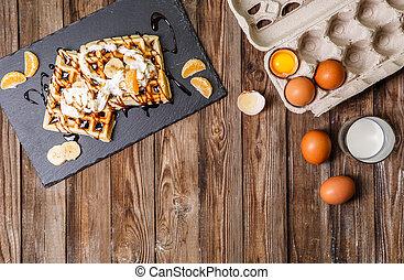 Belgian waffles on wooden table - Belgian waffles, eggs in...