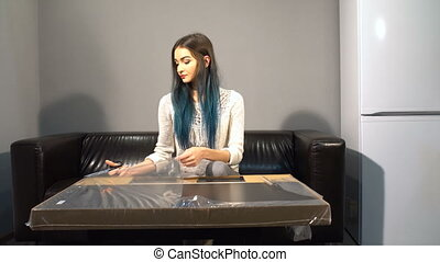 Young cute girl with colored hair sitting on a couch in their new apartment to put together a table. Shoot in kitchen. unpacks the package with scissors