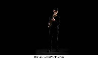 Black background in the studio. Saxophonist playing on the...