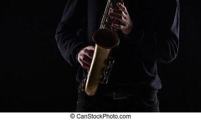 Blues on the saxophone. Musician playing solo in black...