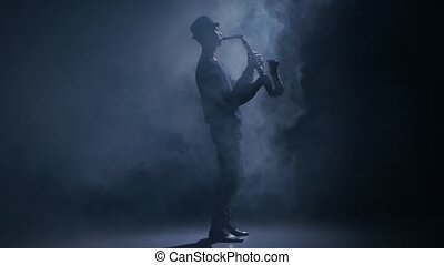 Saxophonist playing a musical instrument in a dark smoky...