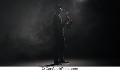 Music saxophone. Performed by man in a dark smoky studio -...