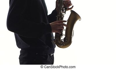 Musician plays an old saxophone. Closeup on white background...