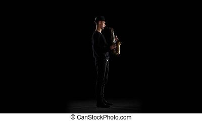 Saxophonist playing on the instrument. Black background in...
